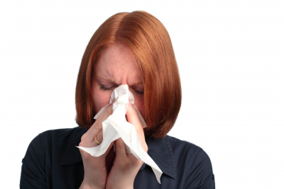 A young woman blowing her nose - because of an allergy or a cold.